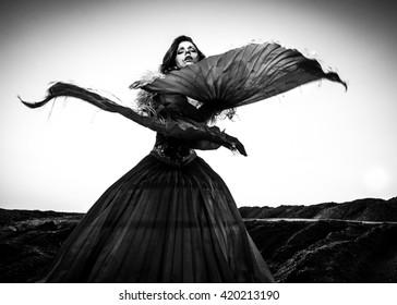 Black-white fine art portrait of attractive romantic woman at fairy tale dry field.