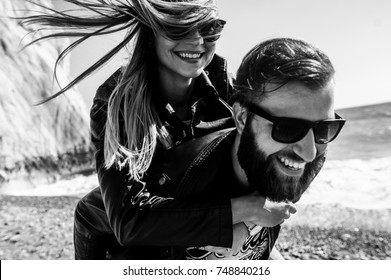 Black&white photo of happy couple in the leather jackets running on the beach