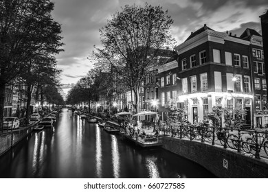 Black-white photo of the most famous canals and embankments of Amsterdam. General view of the cityscape and traditional Netherlands architecture.