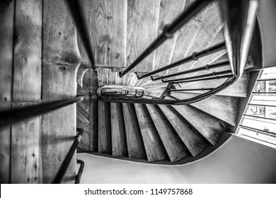 Black-white photo of wooden spiral staircase in old building, Paris, France.