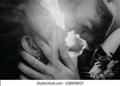 Black-white portrait of the bride and groom close-up. The husband holds his wife by the face against the backdrop of the rays of the sun.