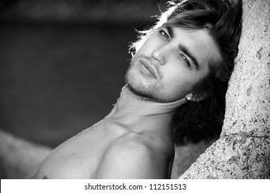 Black-white portrait of a handsome male model posing at the seaside.
