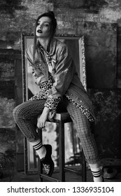 Black-white portrait of a sexy girl in grunge style. Dramatic black and white photo of a beautiful woman on a dark background. Female model in Denim jacket, plaid pants, white socks and leopard shoes.