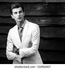 Black-white portrait of young handsome fashionable man in white suit against wooden wall.