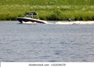 Black-white tow boat with a tower and black bimini top awning towing the water-skier on a background of green Bank-active recreation on the river, water ski, wakeboard, summer