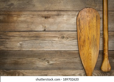 blade and grip of wooden canoe paddle against a wood background with a copy space