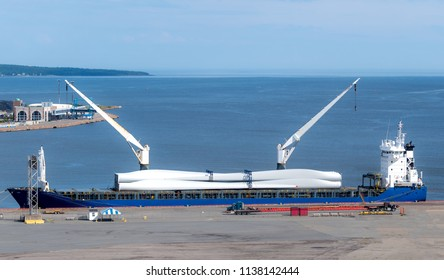 Blades for a large wind turbine being delivered on a ship. The blades are secured on the ship's deck.The ship is equipped with two cranes.
