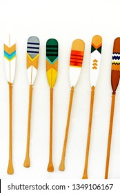 Blades of wooden canoe paddles various colors on the white wall background.