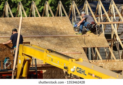Blaine, WA / US - 03/29/2019: Workers complete sheeting on the roof of a new home being constructed in the Semiahmoo Resort community of Blaine, a sign of strong housing market there.