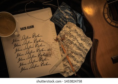 Blaine, WA / USA – July 17, 2019: Illustrative Editorial shot of a music montage showing a classical guitar, music by Bach, a pencil and shavings, nail file, guitar strings and a cup of coffee