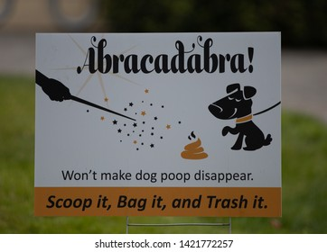 Blaine, WA / USA - June 9, 2019: Illustrative Editorial. White and brown sign in a park urging visitors to pick up after their dog. Abracadabra won't make dog poop dissappear.