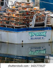 Blaine, WA / USA - June 9, 2019: A gray and white crab boat loaded with colorful traps awaits the opening of crab season reflected in a Northwest harbor, illustrative editorial vertical image
