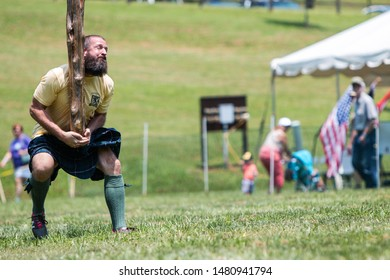 Blairsville, GA / USA - June 9 2018:  A man runs into position to perform a caber toss, at the Blairsville Scottish Highland Games at Meeks Park on June 9, 2018 in Blairsville, GA.