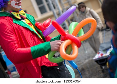 BLAJ, ROMANIA - APRIL 27, 2018: Clown creating balloon animals in different shapes at outdoor festival in city center. Angel wings, butterflies, dogs made of balloons for little girl