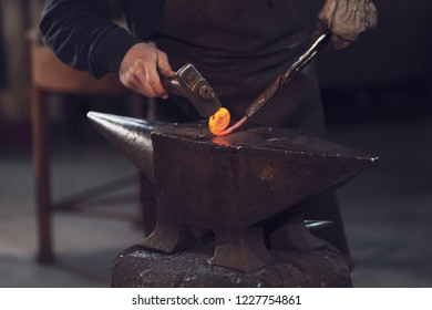 Blaksmith forming a coil with red hot metal from the furnace working with a mallet over an anvil in a close up on the hands