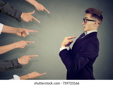 Blaming you. Anxious man judged by different people pointing fingers at him. Negative human emotions feeling
