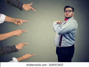 Blaming you. Anxious surprised business man judged by different people pointing fingers at him. Accusation of guilty guy.