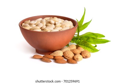 Blanched almonds In a bowl with unshelled nuts. On white background