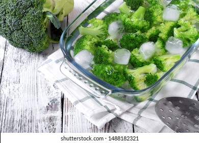 Blanched broccoli cabbage cooling down in cold water in a glass dish on white table