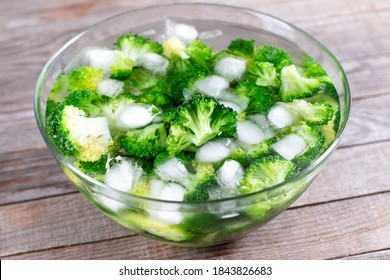 Blanched broccoli cabbage cooling down in icy water in a bowl on wooden table