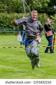 BLANCHLAND, NORTHUMBERLAND, ENGLAND, AUGUST 27. 2018. Man taking part in Sack Race at village fayre. August 27, 2018, Blanchland, Northumberland, England, UK.