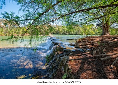 Blanco State Park in Texas showing the waterfall and the treelined river