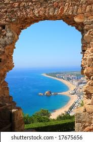 Blanes beach view through an arch  (Costa Brava, Catalonia, Spain)