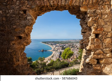 Blanes coastal resort town in Spain, framed above view through hole in a wall of St. John Castle