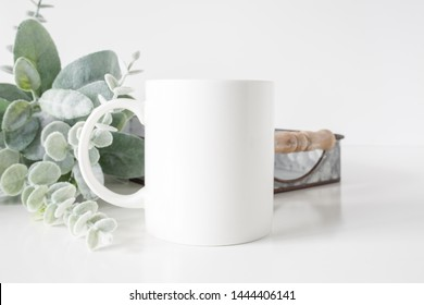Blank 11oz white coffee mug on white background with plant and metal decor, coffee mug mockup