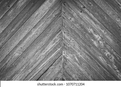 Blank abstract background of gray wooden panels. The surface of a wooden fence is a texture. Diagonal boards. Monochrome image.