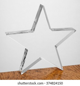Blank acrylic block ready for engraving, star shape, on wooden table