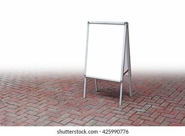 A blank advertisement A-board on a brick floor.