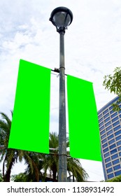 The blank advertising banner suspended on the street lamp pole with the tree and building facade background.