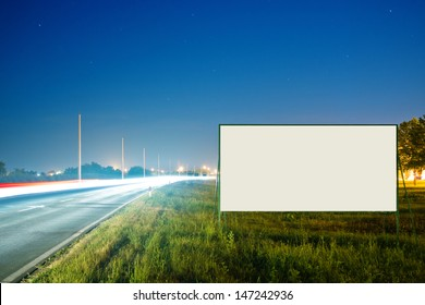 Blank advertising billboard by the busy road at night