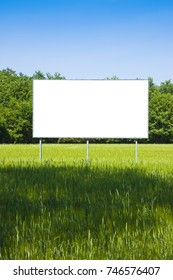 Blank advertising billboard in a green field - image with copy space