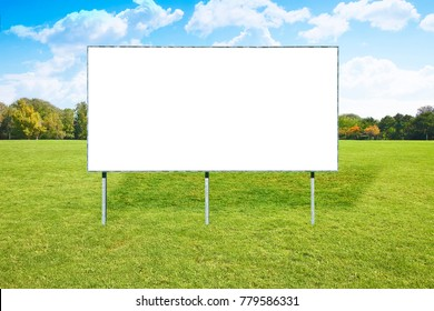 Blank advertising billboard in a green field with trees and sky on background - image with copy space