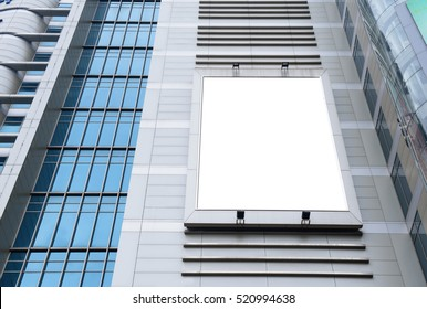 Blank advertising billboard in metallic frame with spotlight on modern office building or outside department store building in the city, useful for advertisement
