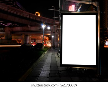 Blank advertising billboard next to bicycle public system at night
