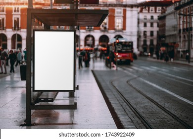 A blank advertising billboard placeholder template on the city street; an empty mock-up of an outdoor poster on a tram stop in Lisbon; a white vertical mockup of an urban banner on the bus stop