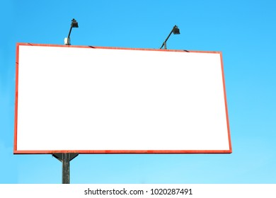 Blank advertising board outdoors against blue sky