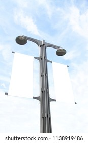 The blank advertising mockup flag suspended on the street lamp pole with blue sky and white cloud background.