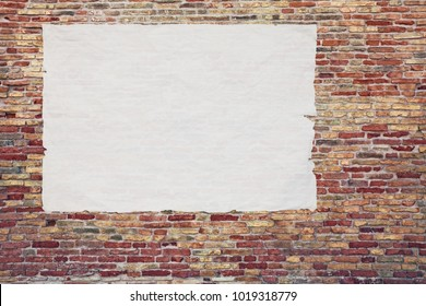 blank advertising poster glued to the brick wall - copy space in street billboard