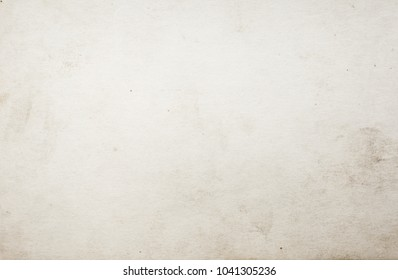 Blank aged paper sheet as old dirty frame background with dust and stains. Front view. Vintage and antique art concept. Detailed closeup studio shot.