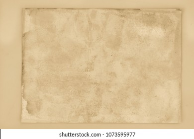 Blank aged paper sheet as old dirty frame background with dust and stains. Front view. Vintage and antique art concept. Detailed closeup studio shot. Black and white toned