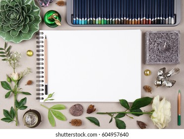 blank album mock up for artwork with colored pencils, decorative elements and natural green leaves. Notebook, sketchpad, sketchbook. View from above