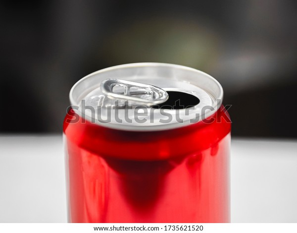 Blank aluminum red soda can. Isolated on blurry background. A single opened soft drink can. 330 ml aluminum beverage drink soda can. Side and top view. Close up. Close up