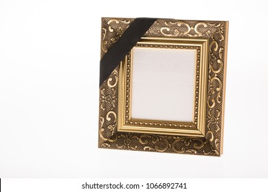 blank antique gold mourning picture frame with black ribbon on bright background for obituary card