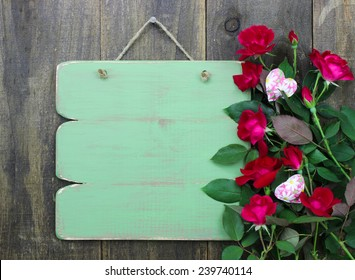 Blank antique green sign with red flower border and floral hearts hanging on rustic wooden background