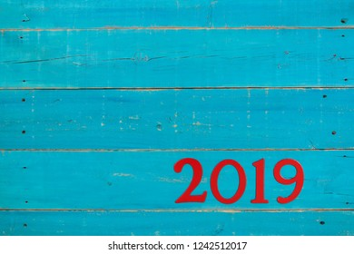 Blank antique rustic teal blue wooden sign with year 2019 in red; Happy New Year holiday concept background with painted copy space