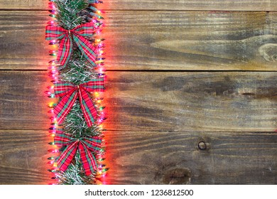 Blank antique rustic wood Christmas sign with garland, colorful lights and red and green plaid bow border; holiday background with copy space